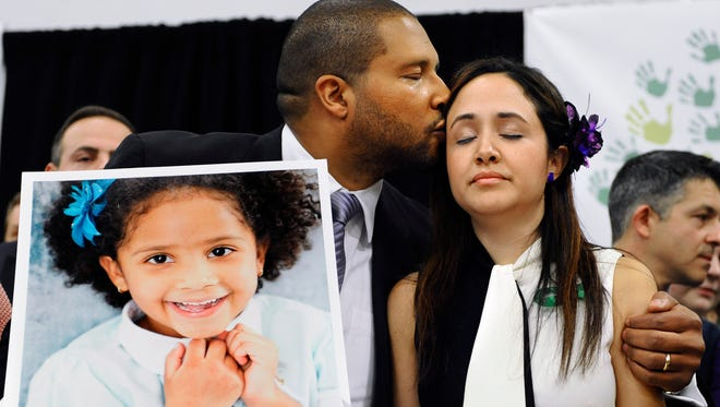 Jimmy Greene, left, kisses his wife Nelba Marquez-Greene as he holds a portrait of their daughter, Sandy Hook School shooting victim Ana  Marquez-Greene at a news conference at Edmond Town Hall in Newtown, Conn., Monday, Jan. 14, 2013.