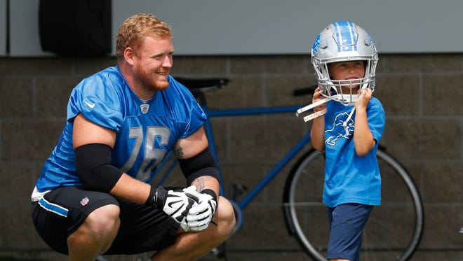 Lions guard T.J. Lang watches his son, J.J., 5, try on his helmet at training camp in Allen Park, July 30, 2017.