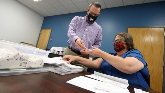 Adam Ragan and Mary Jane Garver prepare mail-in-ballot packages at the Gaston County Board of Elections on West Franklin Blvd. Friday morning, Sept. 25, 2020.