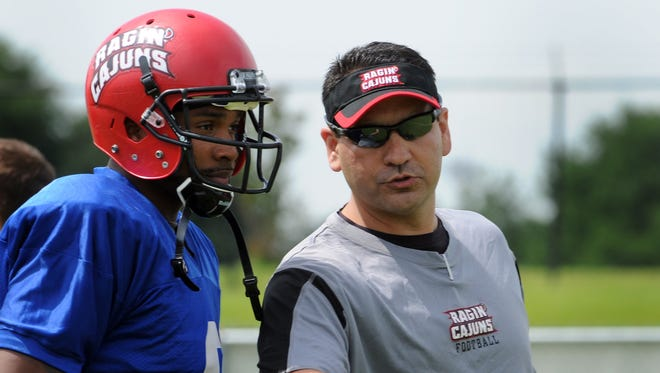 New UL offensive coordinator Jorge Munoz, right, talks with ex-Cajuns quarterback Terrance Broadway, left, before a spring practice in 2012. March 30, 2012