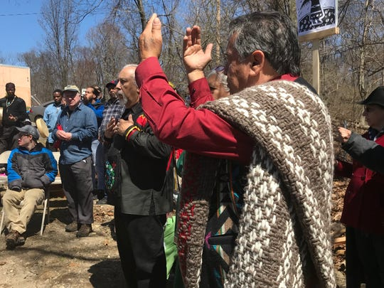Douglas James, one of the carvers of a traveling totem pole, raises his hands in prayer in Mahwah on April 21, 2018 during an event A woman touches a traveling totem pole in Mahwah on April 21, 2018, during an event to unite American Indian tribes across the nation in their opposition to fossil fuel projects.