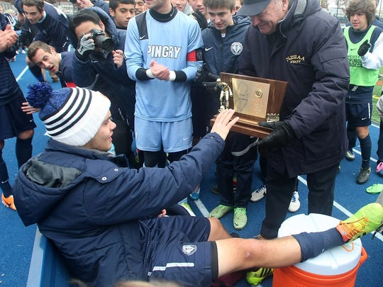 NJSIAA executive director Steve Timko presents injured Pingry player Roberto De Almeida with the Non-Public B state championship trophy.