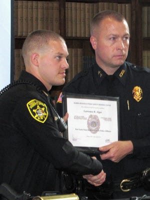 Lawrence Alger, left, of the Tioga County Sheriff's Office, accepts his certificate from Elmira Police Chief Joseph Kane during Friday's graduation ceremony for the Elmira Regional Public Safety Training Center.