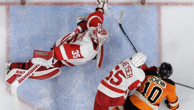 Philadelphia Flyers' Brayden Schenn (10) scores a goal past Detroit Red Wings' Jimmy Howard (35) as Danny DeKeyser (65) tries to defend during the second period of an NHL hockey game, Saturday, March 14, 2015, in Philadelphia.