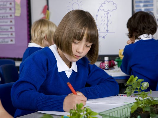 School girl writing in notebook with plant seedlings on desk
