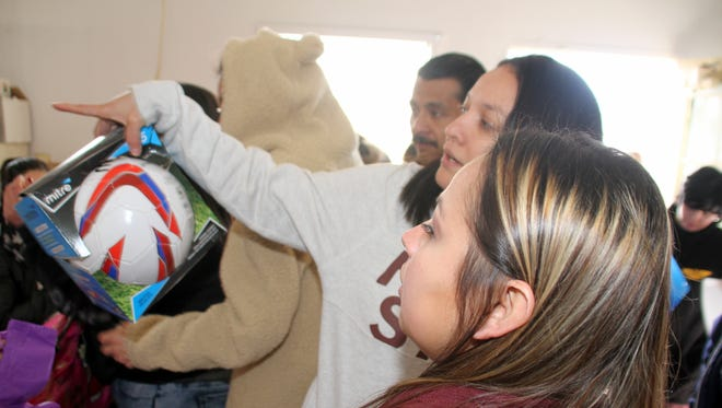 Two family members size up a soccer ball during Saturday's Toys for Tots distribution held at the former Potter's House on the 500 block of East Pine Street in Deming. Close to 800 children received toys that were donated and/or purchased by the Toys for Tots Foundation in Deming and Luna County.