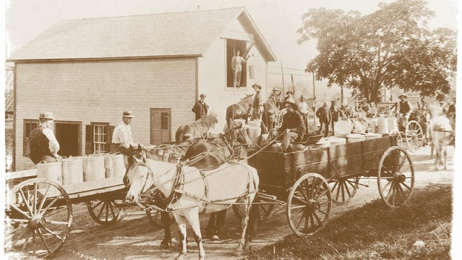 Historic image of horse drawn wagon hauling milk containers to the creamery in Cabot.