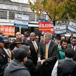 Democratic mayoral candidate Bill de Blasio, center, meets with potential voters on Tuesday, Nov. 5, 2013, in the Crown Heights section of Brooklyn, N.Y.  De Blasio, 52, who as the city's elected public advocate acts as an official watchdog, and has positioned himself as a clean break from Michael Bloomberg.