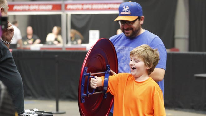 Chase Tarantino, 9, reacts while trying a Captain America shield with his father, JoJo, at Ace Comic Con at Gila River Arena in Glendale, Ariz. January 15, 2018.