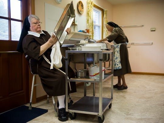 Sister Mary Veronica Jonkier, left, and Sister Jeanne Maffet work to wash and dry dishes following lunch at the Monastery of St. Clare in Evansville, Tuesday, Jan. 17, 2017.