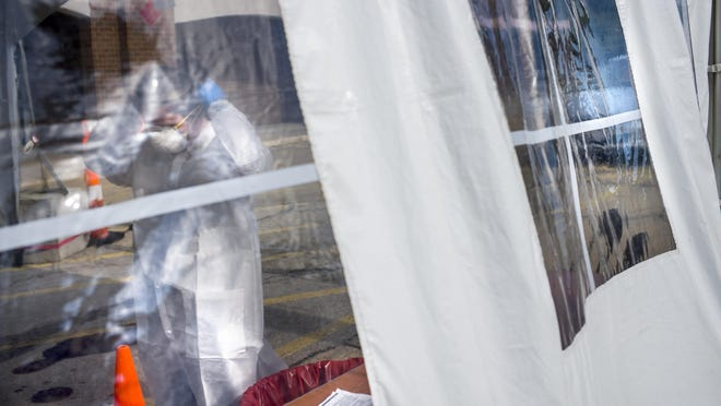 Nurse practitioner Lisa Patel secures her gear seen through the clear plastic window of the drive-through tent for patients arriving in vehicles for COVID-19 testing at Heartland Health Services East Bluff testing site on Wisconsin Avenue in Peoria Friday, June 19, 2020.