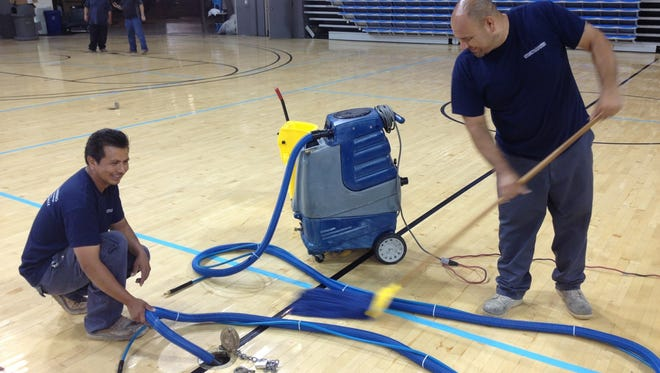 Workers dry off the Pauley Pavilion floor after a water main break Tuesday flooded the facility.
