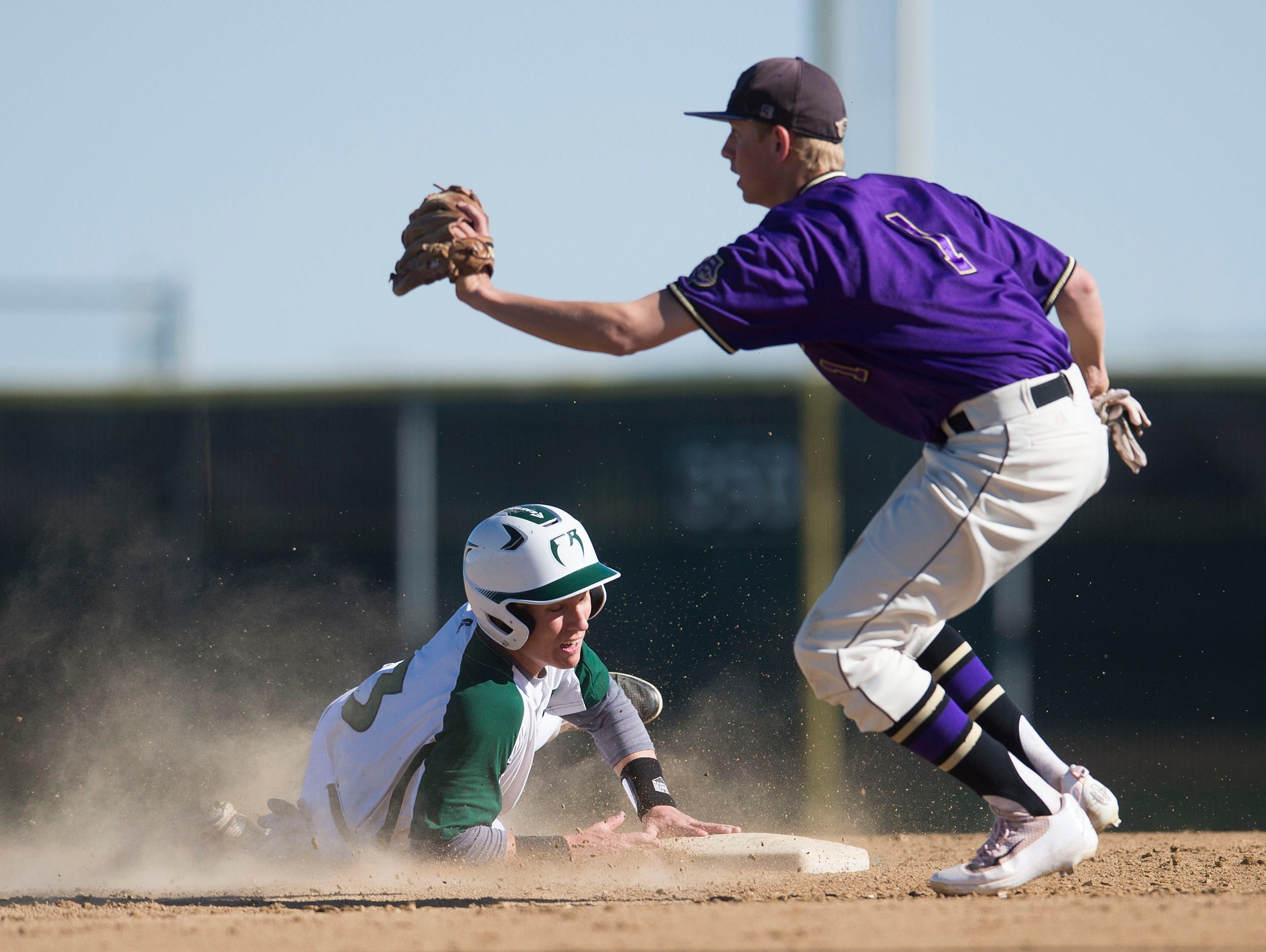 Fort Collins second baseman Jacob Moyer tags out Fossil Ridge baserunner Evan Bergerson as he slides into the base during a game at Fossil Ridge High School Tuesday, May 3, 2016. The SaberCats pulled ahead of the Lambkins to win the game 8-7.