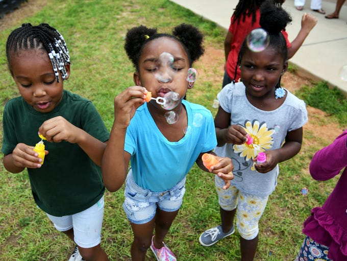 Kylee Jackson, middle, blows bubbles at Grace Christian