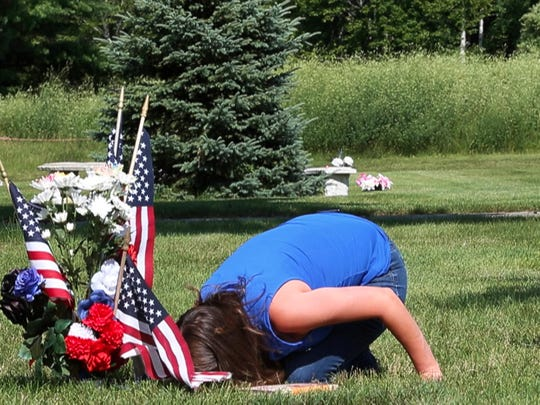 Amy Pierson kisses the grave of her late husband, Officer Daryl Pierson, while visiting his grave in White Haven Memorial Park on Thursday, July 16, 2015.