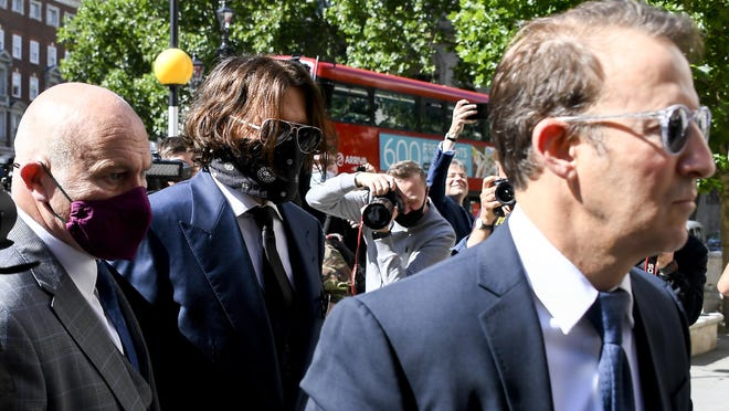 "American actor Johnny Depp (center) wears  protective mask as he arrives at the Royal Court of Justice, in London, Tuesday, July 7, 2020. Johnny Depp has a starring role in a real-life courtroom drama in London, where he is suing a tabloid newspaper for libel over an article that branded him a ""wife beater."" On Tuesday, a judge at the High Court is due to begin hearing Depp's claim against The Sun's publisher, News Group Newspapers, and its executive editor, Dan Wootton, over the 2018 story alleging he was violent and abusive to then-wife Amber Heard. Depp strongly denies the claim."