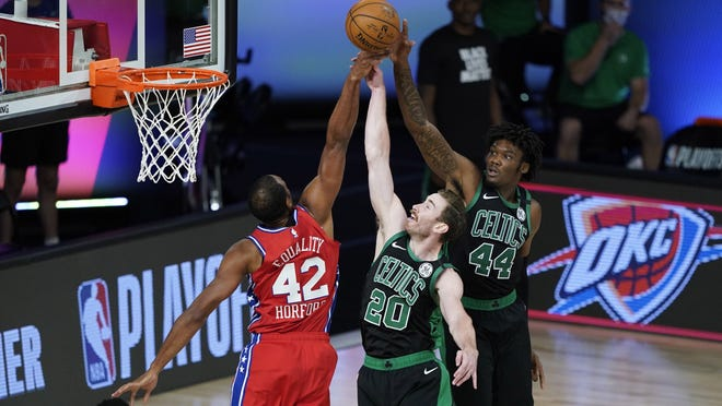 Al Horford (42) goes up for a rebound with Gordon Hayward (20) and Robert Williams III (44) during the first half Monday in Lake Buena Vista, Fla.