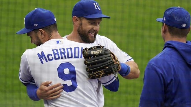 Kansas City Royals left fielder Alex Gordon, middle, is hugged by teammate Ryan McBroom (9) after being taken out of a baseball game against the Detroit Tigers during the second inning at Kauffman Stadium in Kansas City, Mo., Sunday, Sept. 27, 2020. It was Gordon's last game as a Royal.