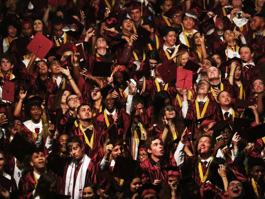 Riverdale High School graduates toss their caps after graduation on Saturday at Germain Arena.