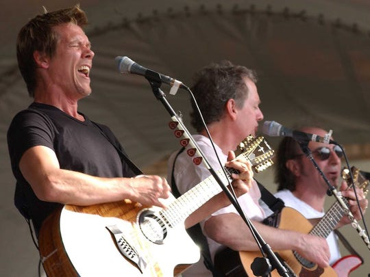 Kevin Bacon (left) and his brother Michael, center, who work professionally as The Bacon Brothers, perform in 2002, in Jacksonville, Fla.