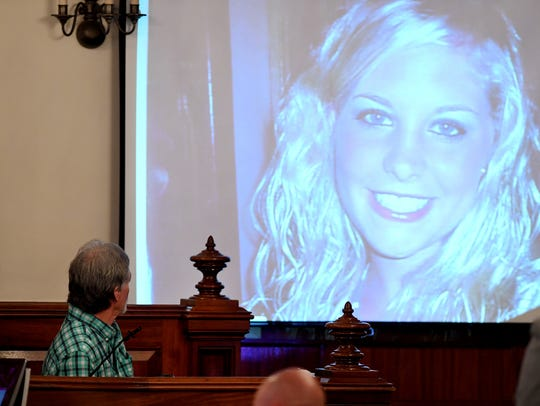 Dana Bobo looks up at a photo of his daughter, Holly