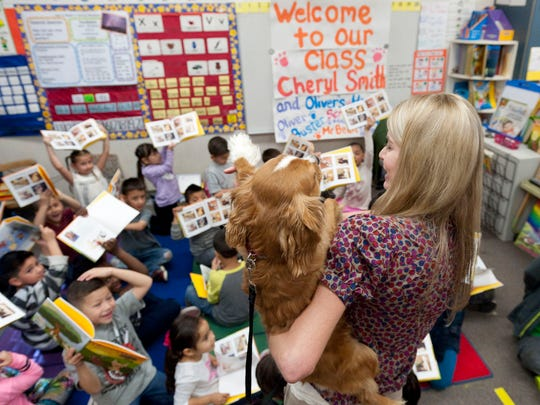 """Cheryl Smith, Tulare County public defender and author of a book about dogs' impact in mental health court, shares her dog Buster with kindergartners at Crestwood Elementary School on Tuesday, March 3, 2015. Each of the students received a copy of her book """"Oliver's Heroes: The Spider Adventures."""""""