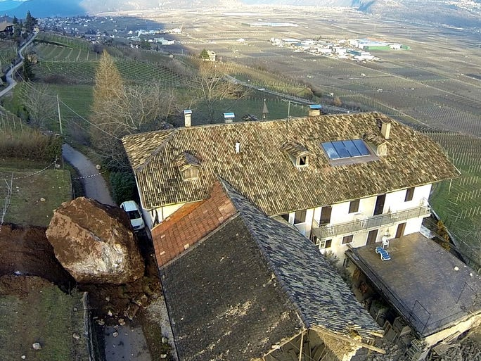 A huge boulder rests next to a home on Jan. 23 in Ronchi di Termeno, Italy. A landslide sent several huge boulders tumbling down a hill, barely missing a home but destroying a barn.