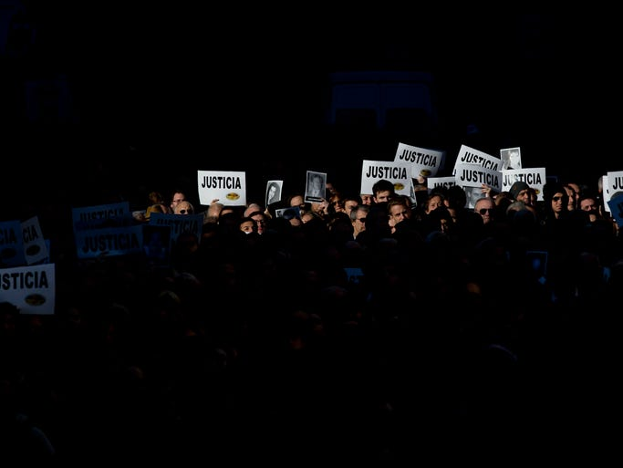 "People hold up signs that read in Spanish; ""Justice,"" and pictures of the victims of the 1994 bombing of the AMIA Jewish community center, during a commemoration ceremony in Buenos Aires, Argentina, Friday, July 18, 2014. Friday marks the 20th anniversary of the unsolved attack that left 85 dead. (AP Photo/Natacha Pisarenko)"