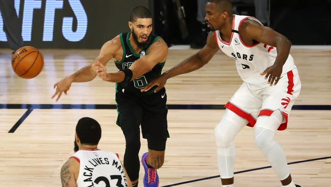 Jayson Tatum passes the ball against Toronto's Fred VanVleet (23) and Serge Ibaka, right, during Tuesday's Game 2 of the second round of the NBA Playoffs. Tatum finished fourth in voting for the league's 2020 Most Improved Player Award.