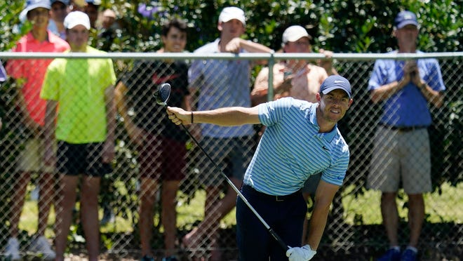 Rory McIlroy watches his tee shot, as do onlookers behind the fence, on the second hole during Saturday's third round of the Charles Schwab Challenge.