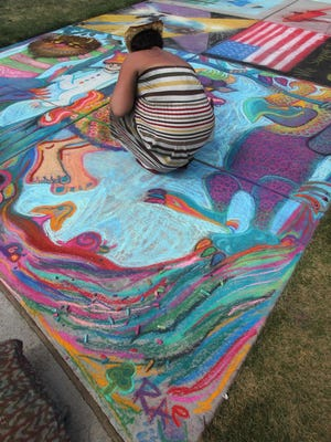 """Raechel Schultz of Wausau works on her drawing based on the book """"Where The Wild Things Are"""" at Chalkfest in downtown Wausau in 2011."""