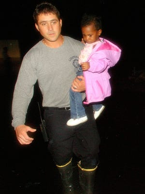 Tallahassee firefighter Lt. Brad Deanda carries Morgan Newman, 1 1/2, to dry ground as she is evacuated late Saturday night, August 23, 2008 in the Timber Lakes neighborhood in Tallahassee, Fla. Torrential rains from Tropical Storm Fay flooded many homes in the neighborhood, and left four feet of water on Timber Ridge Drive, the only way into and out of the subdivision.