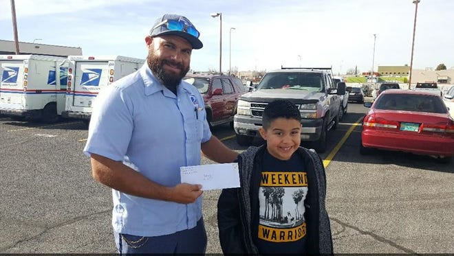 Mailman Erik Davis and Noah Dominguez, who dropped off his letter to Santa on Saturday at the U.S. Post Office in Las Cruces.