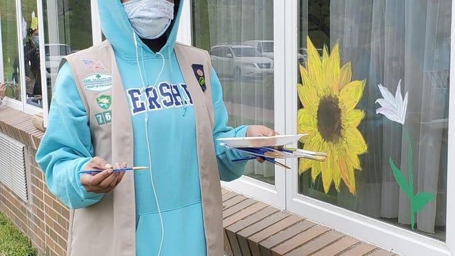 Esther paints a sunflower.