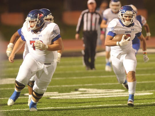 Cooper running back Noah Garcia looks for running room as center Thomas Squyres (70) blocks. Cooper beat Amarillo Palo Duro 49-15 in a District 2-5A Division I game last week.