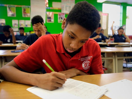 Dayveon  Brown, 12, a seventh-grade student at Carver Academy in Milwaukee Public Schools, reviews math problems Friday. Carver students come to school in uniforms, a policy the school district plans to extend to all schools in the fall.