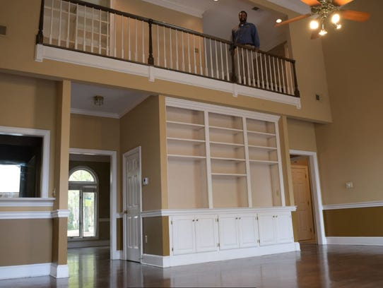 Realtor Thomas Byrd looks over the great room, which