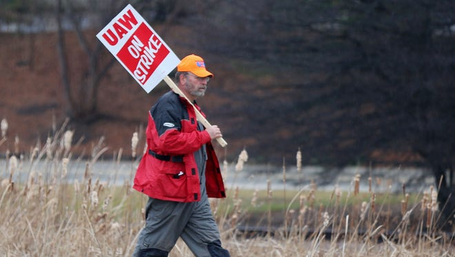 A striking UAW Local 833 Kohler worker walks near the picket line along County Road PP Thursday, Nov. 26, in Kohler.