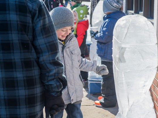 Cody Oberholzer smiles when he sees an owl ice sculpture at IceFest on Saturday, Jan. 30, 2015 in Chambersburg, Pa.