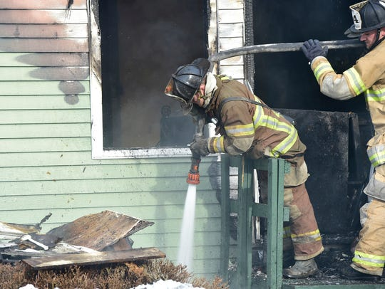 Firefighters extinguish hot spots at a house fire Sunday,
