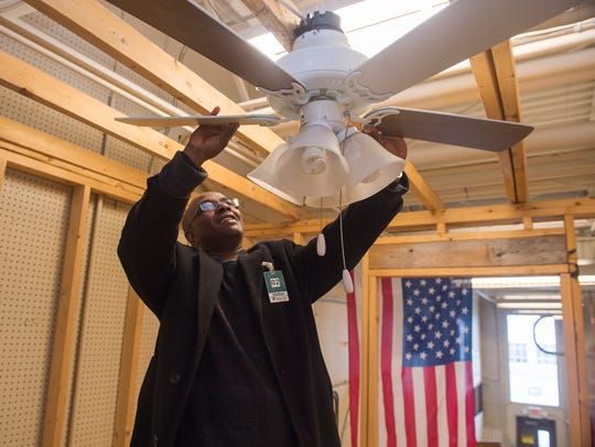 Alexis Robinson inspects a fan that he learned to install