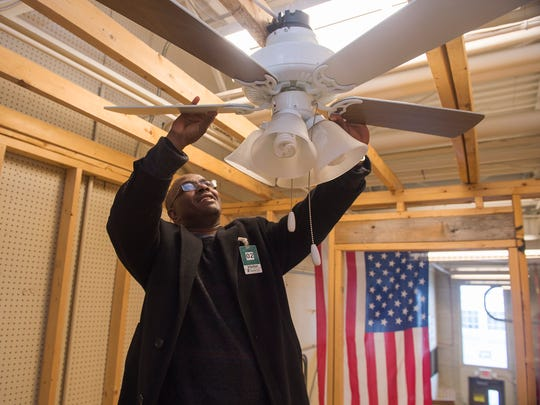 Alexis Robinson inspects a fan that he learned to install in a practice model frame for a residences at the Franklin County Career and Tech Center on Wednesday, Feb. 10, 2016.  Robinson wants to take back what he learned and open a professional school in Haiti.