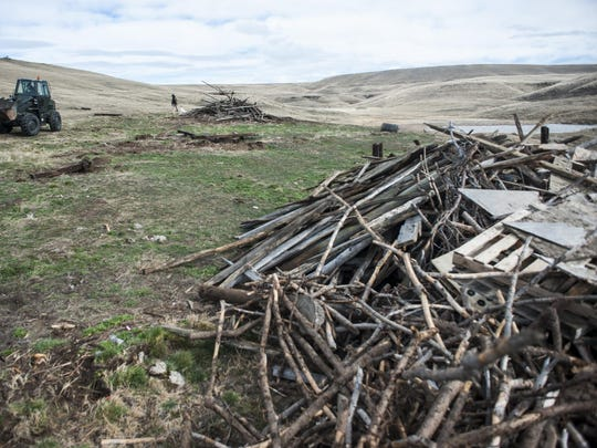 """Montana Department of Natural Resources and Conservation employees clean a dump site on DNRC recreational land Tuesday. """"We want people to use land where it's legally accessible but with that comes respect. This kind of abuse is damaging and costly,"""" said Andy Burgoyne."""