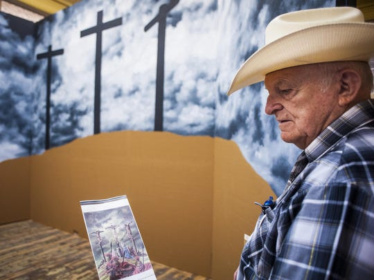 Bob Watts holds a pamphlet showing what his mural will resemble when finished. The Forsyth artist, primarily known for crowbar paintings, is creating a Styrofoam western town with murals telling the story of the life of Christ hidden behind doors, windows and storefronts.