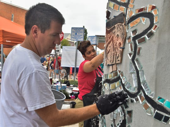 Nathan Rotz, left, and Kristen Lovett work on the mural on Saturday, July, 16, 2016 in Chambersburg, Pa.