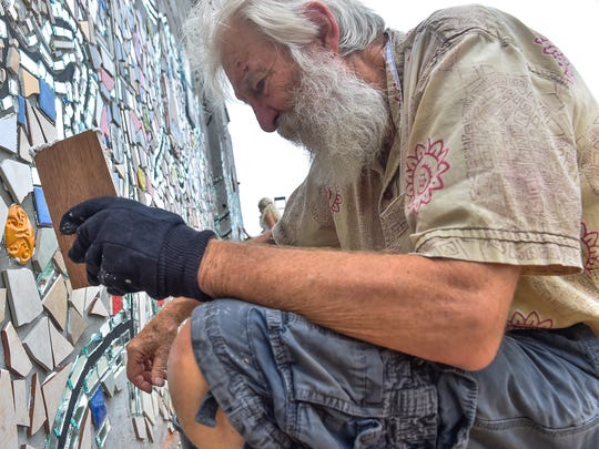 Isaiah Zagar glues a piece of tile onto part of a muralc being created on the wall outside of Main Street Deli on Satueday, July 16, 2016 in downtown Chambersburg, Pa. Zagar will be creating two mosaics in downtown.