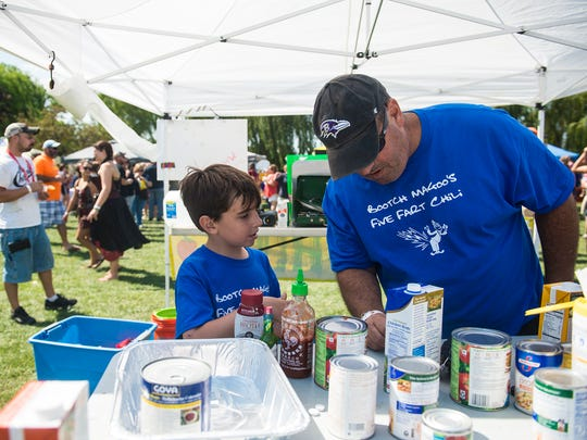 Jeremy Levy, 9, and his father, Matthew Levy, both of Cockeysville, Md, consult on the chili-making process on Sept. 4, 2016 at Goode Field.