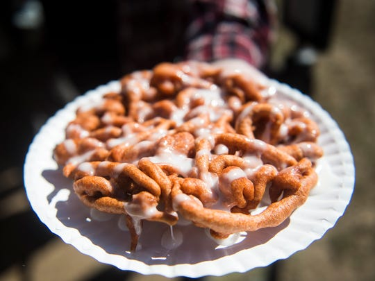 A festival goer holds out a freshly made pumpkin funnel cake, one of the many food offerings available at the Apple Harvest Festival on Sunday.