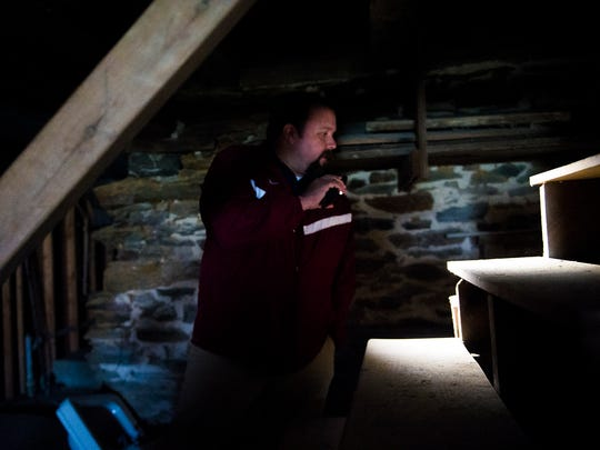 Hanover public works director A.J. Grimm  uses a flashlight to scan the basement's staircase at the historic Fisher-Crouse House.