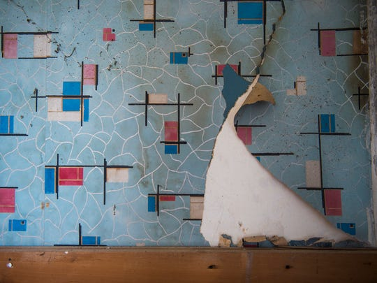 Wallpaper from different eras is revealed on a peeling wall at the Fisher-Crouse House.